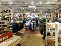 购物衣裳的人们在时尚购物中心商店 免版税图库摄影