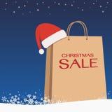 购物袋在雪蓝色背景的圣诞老人帽子 库存图片