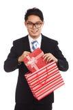 从购物袋的亚洲商人拉扯礼物盒 图库摄影