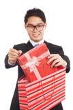 从购物袋的亚洲商人拉扯礼物盒 库存图片