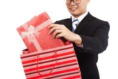从购物袋的亚洲商人拉扯礼物盒 免版税库存图片