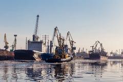 货物起重机、散货船和拖轮在口岸 免版税库存照片