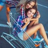 购物车的两个愉快的美丽的女孩户外,生活方式c 免版税库存照片
