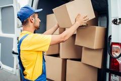 货物送货业务,男性传讯者卸载卡车 免版税库存照片