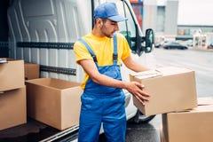 货物送货业务,男性传讯者卸载卡车 库存照片