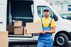 货物送货业务,男性传讯者卸载卡车 免版税库存图片
