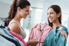 购物选择衬衣在商店的女孩 免版税库存照片