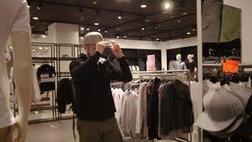 购物,时尚,样式-胡子年轻人选择在购物中心或服装店的盖帽 影视素材
