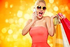购物 年轻微笑的妇女拿着袋子的和手机在黑星期五假日做她的赞许 黄色的女孩 库存照片