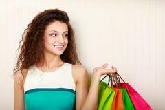 购物-有袋子和金钱的少妇 库存照片