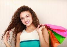 购物-有袋子和金钱的少妇 图库摄影