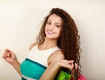 购物-有袋子和金钱的少妇 免版税库存照片
