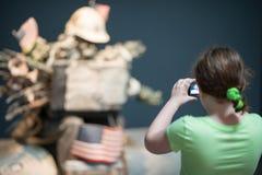 特伦顿, NJ - 2017年6月17日:拍与艺术展览她的照相机的女孩一张照片在雕塑的地面 库存图片