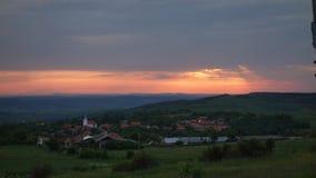 从特兰西瓦尼亚,德雷库拉土地的小村庄,一个小谷的,在日出 美丽的天空,橙色颜色,掩藏在云彩 免版税库存图片