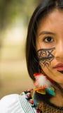 特写美丽的似亚马逊妇女、本地产的面部油漆和耳环有五颜六色的羽毛的,严重摆在为 免版税库存照片