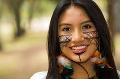 特写美丽的似亚马逊妇女、本地产的面部油漆和耳环有五颜六色的羽毛的,愉快地摆在为 免版税库存图片