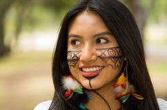 特写美丽的似亚马逊妇女、本地产的面部油漆和耳环有五颜六色的羽毛的,愉快地摆在为 库存照片