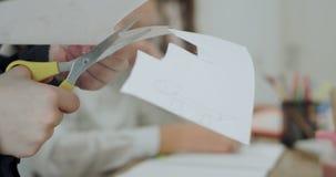 特写镜头一个小孩子删去了学校家庭作业的白皮书,在他用黄色慢慢地切开的照相机前面 影视素材