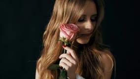 特写镜头一个美好的模型的演播室画象与一朵花的在她的手上 4k慢动作 股票录像