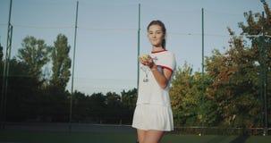 特写镜头一名俏丽的妇女在手上打网球,看直接对照相机,晴天外面 股票视频