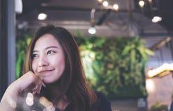 特写镜头一名美丽的亚裔妇女的画象图象有坐在与感到的现代咖啡馆的兴高采烈的面孔的好 免版税库存照片