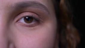 特写镜头一固定和严重眨眼睛和观看入照相机的年轻深色的有波浪头发的学生眼睛画象  股票录像