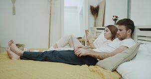 特写镜头一对年轻夫妇一起有一美好时光在舒适床,女性读书看通过笔记本的一个书人 股票录像