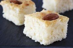 特写镜头三个片断Basbousa传统阿拉伯粗面粉蛋糕用杏仁胡说的橙色开花水 复制空间 库存图片