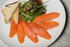 特写镜头三文鱼切片服务用rucola和蕃茄沙拉并且敬酒了面包 库存图片