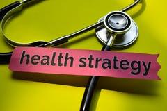 特写镜头与听诊器概念启发的健康战略在黄色背景 免版税库存照片