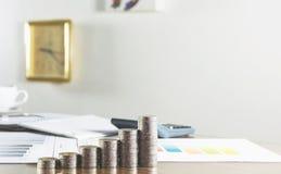 特写镜头与文件的堆硬币在工作表和时钟上 免版税库存图片