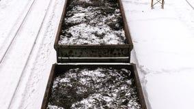 特写镜头与金属削片的货物vagons在火车站的路轨中在冬天 影视素材