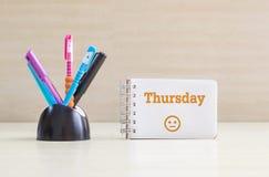 特写镜头与黑陶瓷书桌的颜色笔整洁为笔和桔子在白页的星期四词和正常面孔情感在笔记 免版税库存图片
