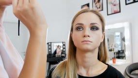 特写镜头专业化妆师绘的眼睛和申请染睫毛油慢动作录影  准备模型的Visagiste 股票视频