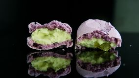 特写镜头两一半与反射的残破的紫罗兰色法国macaron 影视素材