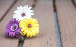 特写镜头五颜六色的伪造的花为在被弄脏的老木桌织地不很细背景装饰 免版税库存图片