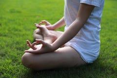特写镜头亚洲中国人说谎的放置在认为草的草坪做在森林公园阳光太阳健康好日子的凝思的瑜伽姿势 图库摄影