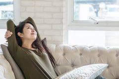 特写镜头亚裔妇女在她的业余时间的沙发放松在屋子背景里 图库摄影