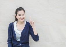 特写镜头亚裔妇女阻止与微笑面孔的一手指行动在与拷贝空间的大理石石墙被构造的背景 库存照片