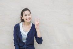 特写镜头亚裔妇女阻止与微笑面孔的三个手指行动在与拷贝空间的大理石石墙被构造的背景 免版税图库摄影