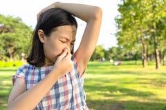 特写镜头亚裔逗人喜爱的女孩在室外公园感觉坏肮脏的气味情况,嗅到,嗅她的湿腋窝,漂亮的孩子 免版税库存图片