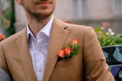 特写镜头人在与三朵玫瑰的优等的jaket穿戴了在poket 免版税库存照片