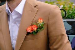特写镜头人在与三朵玫瑰的优等的jaket穿戴了在poket 免版税库存图片