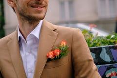 特写镜头人在与三朵玫瑰的优等的jaket穿戴了在poket 库存图片