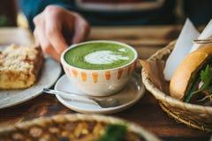 特写镜头人拿着杯子与美好的样式的绿茶的` s手以白色泡沫的形式在点心旁边和 免版税图库摄影