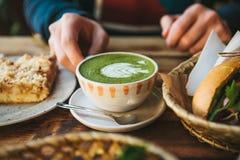 特写镜头人拿着杯子与美好的样式的绿茶的` s手以白色泡沫的形式在点心旁边和 库存图片