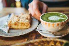 特写镜头人拿着杯子与美好的样式的绿茶的` s手以白色泡沫的形式在点心旁边 图库摄影