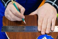 特写镜头人` s手画在统治者的一支铅笔与删去的家具细节一块不标准的模板在旁边 库存图片