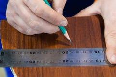 特写镜头人` s手画在统治者的一支铅笔与删去的家具细节一块不标准的模板在旁边 免版税图库摄影