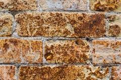 特写镜头从一块古老黄色葡萄酒砖的背景墙壁与表面上的生锈的腐蚀样式 织地不很细 免版税库存图片